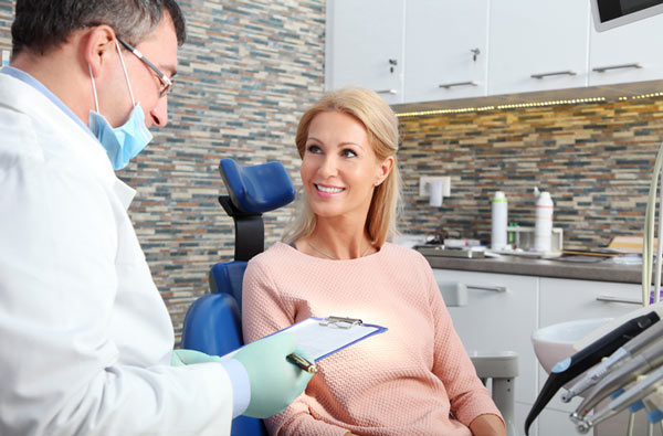 Woman talking to dentist during dental exam at Eastside Dental Clinic in Troutdale, OR