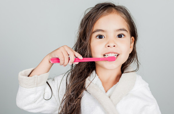 Young girl brushing her teeth after dental appointment at Eastside Dental in Troutdale, OR